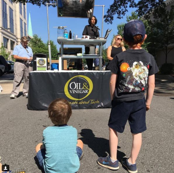 Two kids watching the Oil and Vinegar cooking demo
